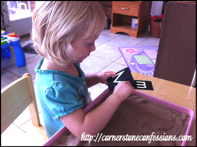 Tracing sandpaper letters and then writing the letter in sand